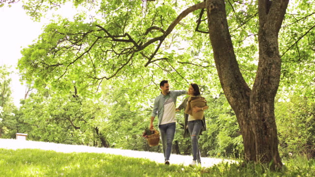 Happy couple in love going on picnic and enjoying in  spring day at the park.