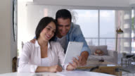 Happy couple looking at pictures on a tablet