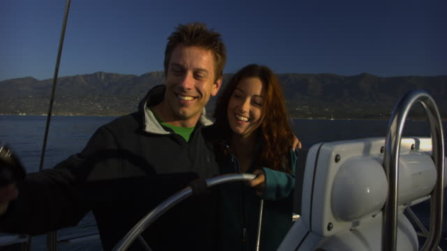 CU Happy couple photographing self at wheel on yacht, Santa Barbara, California, USA