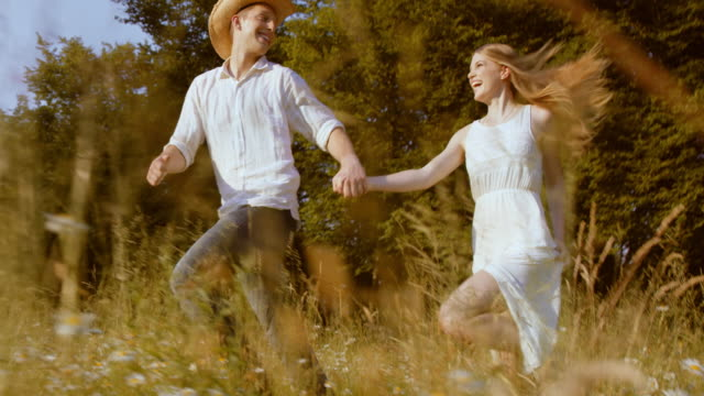 SLO MO TS Happy couple running across meadow in sunshine