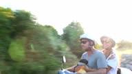 Happy couple scooter adventure in golden evening sunlight