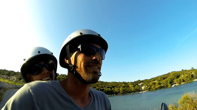 Happy couple scooter adventure on island holiday Slow Mo