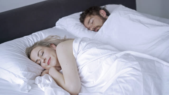Happy couple sleeping pleasantly in their bed