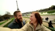 Happy couple taking selfie at the Eiffel Tower, Paris