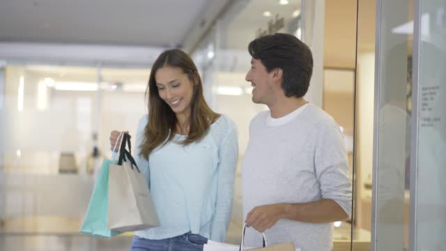 Gelukkige paar lopen uit een winkel op zoek zeer tevreden