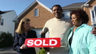 Happy Couple with Agent Holding SOLD Sign