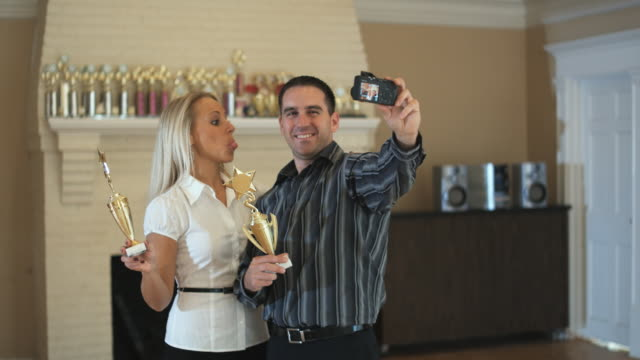 MS, Happy couple with trophies photographing self in dance studio, Hingham, Massachusetts, USA