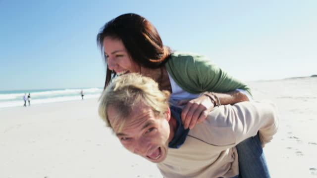 Happy Couple: woman jumping onto mans back