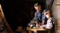 Happy dad teaches daughter about woodwork