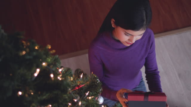 Happy excited woman opening gift box, Home video, Camera top view.