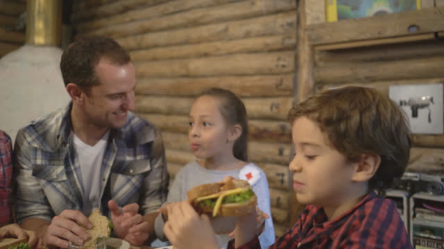 Happy family enjoying sandwiches for dinner