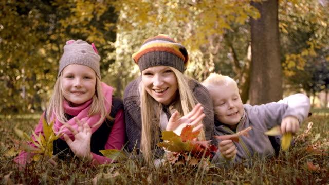 Famiglia felice che si diverte nel parco d'autunno