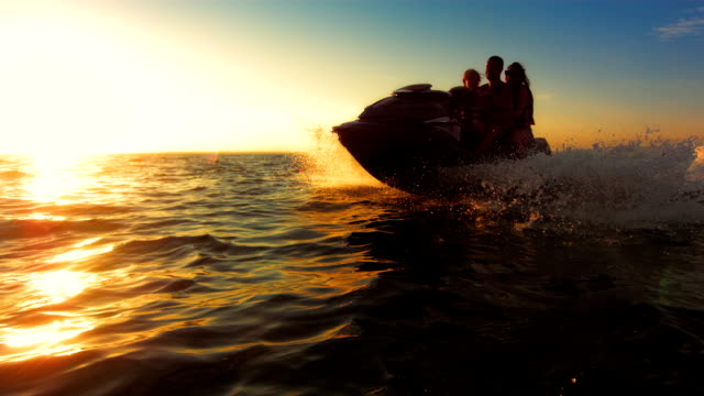 SLO MO Happy Family Riding A Jet Boat At Sunset