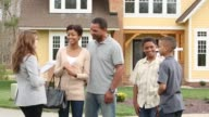 WS Happy Family shaking hands with realtor in front of suburban house with for sale sign