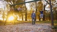 SLO MO Happy family swinging in the park