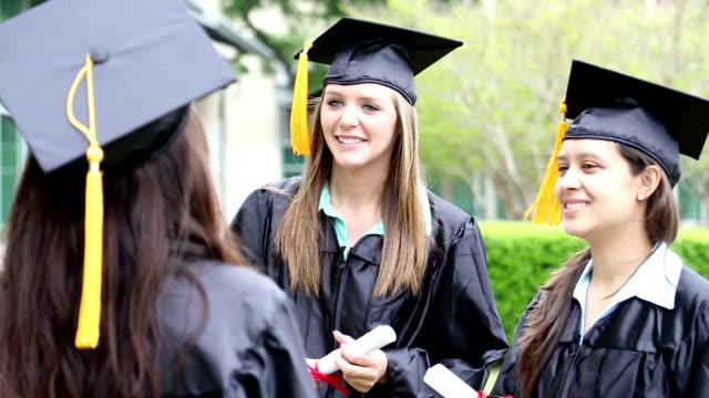 Happy female graduates talking on graduation day