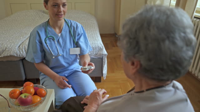 Gelukkig vrouwelijke verpleegkundige receptplichtige geneesmiddelen te geven aan een oude vrouw die ze afwijst en het nemen van de vrucht in plaats daarvan.