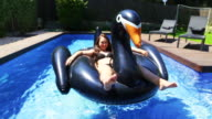 Happy girl enjoying summer in swimming pool with big inflatable black swan sunbathing and relaxing in the sun during weekend.