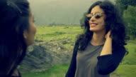 Happy girl with her female friend enjoying vacation in hills.