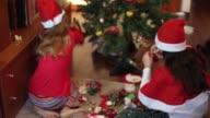 Happy girls decorating the Christmas tree.