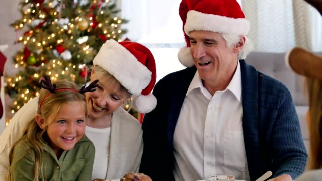 Happy grandma and grandpa enjoy Christmas dinner with their granddaughters