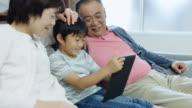 Happy Grandparents Watching Boy with Tablet Computer