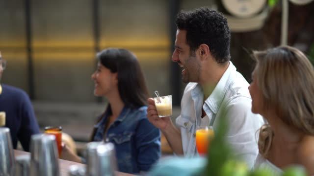 Gelukkig groep vrienden aan de bar zitten teller met dranken