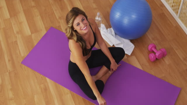 Happy healthy young woman smiling on workout mat