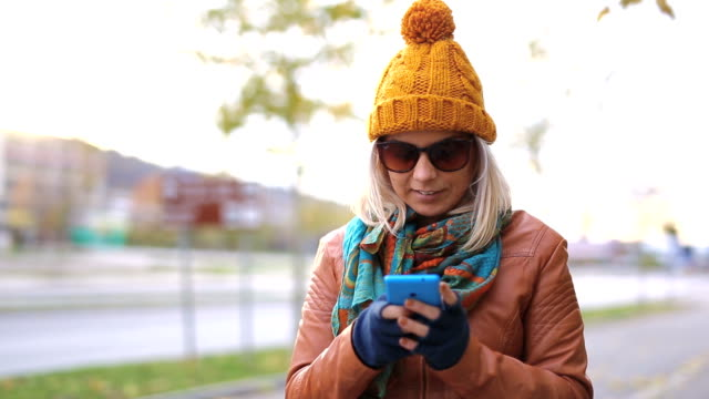 Happy hipster woman typing text message in the city