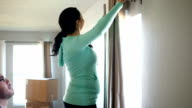 Happy Hispanic couple hanging curtains in new home after moving in