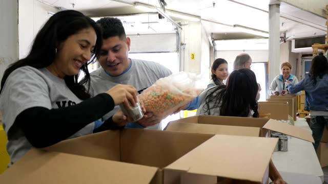 Happy Hispanic couple sorting donations with diverse group of volunteers