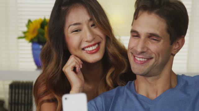 Happy interracial couple taking selfies
