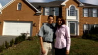 Happy Latin Couple in Front of Home