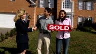 Happy Latin Couple with Agent Holding a SOLD Sign