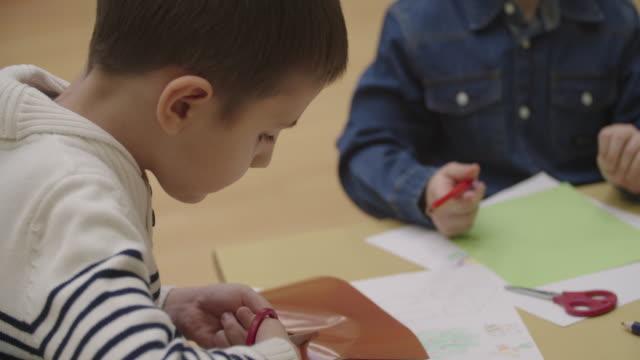 4K: Happy Little Boy using scissors in kindergarten.