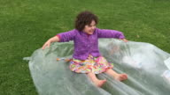 Happy little girl being pulled on a plastic sheet.