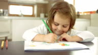 Happy Little Girl Drawing Behind A Table
