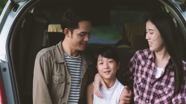 Glückliche kleine Mädchen mit asiatischen Familie sitzt im Auto für die Straße Reise und Sommer Urlaub im Wohnmobil