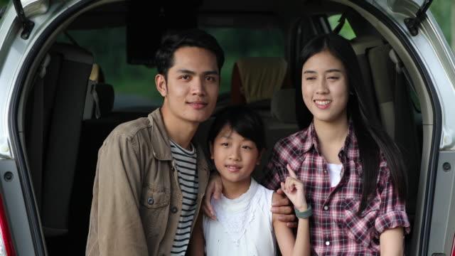 Gelukkig klein meisje met Aziatische familie zitten in de auto om te genieten van de weg reis en in de zomer vakantie in kampeerauto