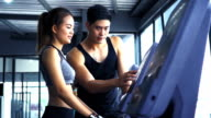 Happy male instructor looking at female client exercising on treadmill in health club