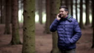 Happy man in a forest talking