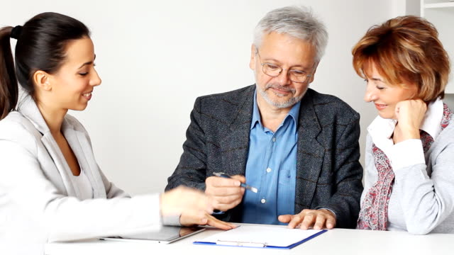 Happy Mature Couple in Meeting With Financial Advisor