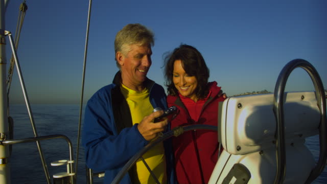 MS Happy mature couple photographing self at wheel on yacht, Santa Barbara, California, USA