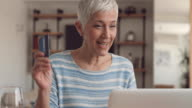 Happy mature woman shopping online with credit card and laptop at home.