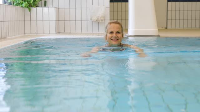 Gelukkig volwassen vrouw zwemmen in zwembad op sportschool