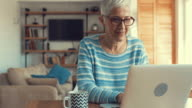 Happy mature woman typing e-mail on laptop and looking at the camera.