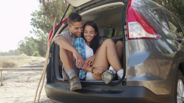 Happy Mexican couple sitting together in the car