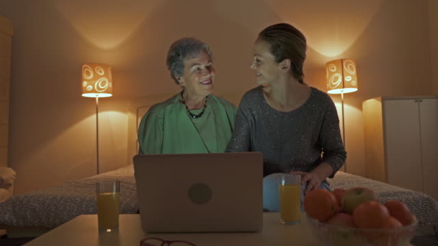 Happy mid adult woman and her mother having video chat over laptop and waving to someone.