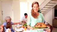 Happy mother showing roast turkey to camera