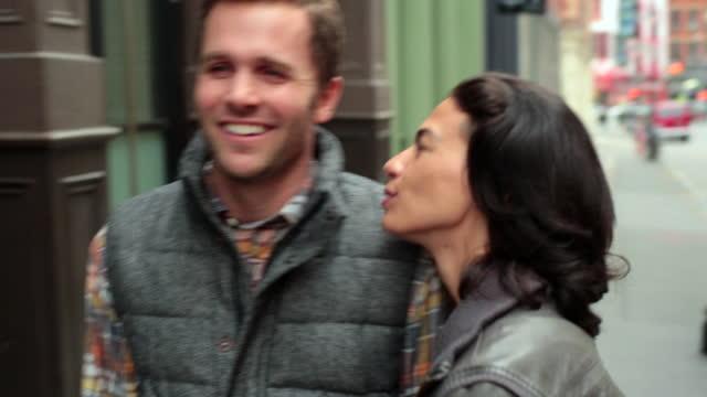 Happy New York couple walk arm-in-arm up sidewalk in Soho, girl kisses boyfriend's cheek